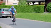 handheld : VRHNIKA, SLOVENIA - JUNE 2014: Handheld shot of bicyclist speeding on road. Very fast cyclist on professional bike competing in a race around countryside.
