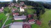 sídelní struktura : CELJE, SLOVENIA - SEPTEMBER 2014: Small village with the church in a countryside in nature. Aerial fly over shoot of small village with the church in a countryside in nature Dostupné videozáznamy