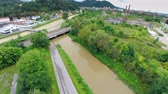 flooded road : Aerial shot of muddy river flooding under railway bridge. Wide shot of rising rivers joining together. Flying over static shot.