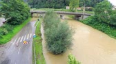flooded road : Ascending over flooding river and closed road. Flying over a river flooding lower parts of road, which is closed for vehicles. Stock Footage