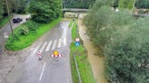 flooded road : Sign for closed road with car stuck in water. Aerial flying above road which is flooded under the bridge with warning sign for drivers. One car stuck in water. Stock Footage