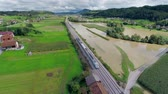 flooded road : Flying behind passenger train. Aerial shot of train travel through sunny countryside while green fields are flooded with muddy water.