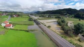 flooded road : Aerial landscape with train on tracks and flooded fields. Wide shot of flooded valley with train tracks in the middle and white clouds in the sky. Stock Footage