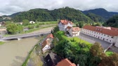 flooded road : Aerial of city bridge with very high level river. Celje city in Slovenia with small castle on top of hill beside a muddy river after massive rainstorm.