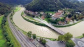 flooded road : Flying over river making curve through town to valley. Wide aerial shot of river running through Celje city making a turn in to valley. Stock Footage
