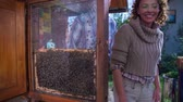 cera de abelha : Tourist couple leaves the local beehive. Slow motion RAW footage of a tourist couple who is imprest bay hard working bees and then go on there way on a sunny day. Vídeos