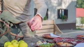 pack : Man picking up the salami and pack it in to the bag . Slow motion close up RAW footage of a home made salami being picked up and packed in to the green bag by a men at the garden table of the restoration in the countryside. Stock Footage