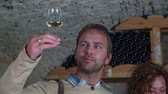 connoisseur : Couple checking the colour of a good wine . Slow motion close up RAW footage of a couple in the wine cellar tasting the wine and checking the colour of it in the domestic restoration. Stock Footage