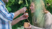 week end : Man giving the woman a honey in to the cup of tea . Close up RAW footage of a men sweating the women tea with honey with wooden sponge in the middle of  a countryside.