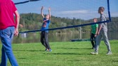 voleibol : Young boy serving to start the volleyball play . Slow motion RAW footage of a young cute boy serving to start to play the game of volleyball near the lake on a sunny day.