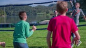 voleibol : Beautiful day for volleyball in the park . Slow motion close up RAW footage of a grope of a kids playing the volleyball on a lawn close to the lake on a sunny day.