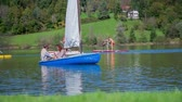 surfe : Couple enjoining on the boat sailing on a lake. Slow motion RAW footage of a boat sailing on the lake and surfers paddling in the beck ground on a sunny day. Vídeos