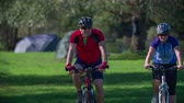 surfe : Couple on Sunday cycling  . Slow motion close up RAW footage of a couple on the bicycles sporting near the river in the middle of a countryside on sunny day.