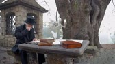 compositor : Educated man thinking at the garden table. Slow motion total RAW footage of a man from romantic time seating at the stone table on a garden on a nice day.