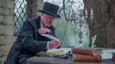 escrita : Poem written with a feather pan. Slow motion RAW footage of a man from romantic times seating at stone table and writing a poem with a feather pan.
