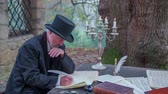 compositor : Man from romantic times writing outdoors. Slow motion RAW footage of a man from modern times seating at stone table under the tree and writing a poem on nice day.
