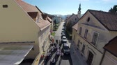 tower : Zoomingout helicopter camera flaying above the parade going through the village on a beautiful sunny day. Stock Footage