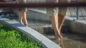 trough : Couple walks on stairs covered with water . Close up RAW footage of a couple walking trough the small pools barefoot with therapeutic water on a sunny day.