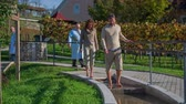 trough : Couple tests the therapeutic pools. Slow motion RAW footage of a middle age couple walking trough the therapeutic on a sunny day.