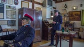 trough : Room in the train station museum . Slow motion RAW footage of a conductor walking trough the room in the train station museum to get some documents.
