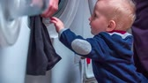 arruela : Learning how you wash the clothes. Young cut boy standing at washer and looking mother how she is putting clothes in a washer in bathroom.