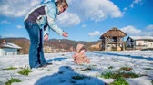 deslizamento : Mother and young child boy outdoors playing on a snow on a sunny day in countryside. Stock Footage