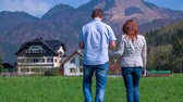 trough : This two middle-aged people walking trough the beautiful green grass in a beautiful nature on a countryside.