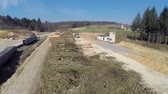crane : Next to the building side are standing big piles of logs on a sunny day in the middle of a countryside, footage is taken with helicopter camera.