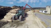 crane : Tractor standing next to the big pile of wood and clinging it with a big mechanical arm in the middle of a countryside. Stock Footage