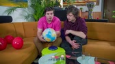 sex : homosexual couple is seating on a sofa and looking at a globe so they know where they are going to travel.