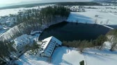 roof : Helicopter camera zooming out on a lake in the middle of a beautiful land scape on a snowy winter day. Stock Footage