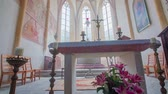 soul searching : The church altar in the front. Two blowing candles on the side. There is a cross on the altar. In the background, there are windows and statues. Beautiful interior design with carpets and chairs and flowers