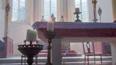 soul searching : Church altar with a blowing candle in the front. In the background, there are statues and windows.