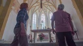 soul searching : An older Christian couple is coming to the church altar and observing the cross that is hanging down the church ceiling. In the background, there are windows, burning candles and statues. In the front there are stairs. Stock Footage