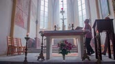 soul searching : Two older Christians walking around the altar and looking up in the church. Cross on the altar. Beautiful windows, church paintings and chairs in the background. Indoor design is fascinating. Burning candles in the front. Stock Footage