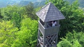 color : A young couple is going up the stairs to the top of the lookout tower. The tower is shot from the sky