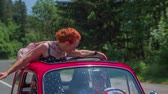 pár : A senior lady is enjoying the ride in a small red vintage car. She circles with her arms and is smiling. There are a few cars driving behind the zastava car. The weather is sunny. Dostupné videozáznamy