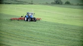 tenure : Blue tractor with attachment is working with grass on nice green lawn in a very nice environment on a very authentic countryside. Stock Footage