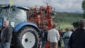 tenure : AGRICULTURAL FAIR EVENT DRAMLJE JULY 2015: Tractor with attachment is positioned at a glance on the agricultural fair which is positioned in the middle of green nature on great landscape on countryside.