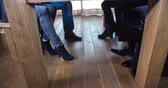 comunicação : Four people are having a business meeting and then suddenly they are starting to tap with their feet. Close-up shot.