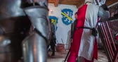 pár : There are many armours in one room and a few knights are getting dressed. Close-up shot.