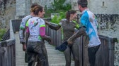 curso : EVENT URBANI GLADIATOR CELJE 2016 This team of four participants is taking a photo together. Then they are going to wash the dirt from the mud pool of themselves. Close-up shot.
