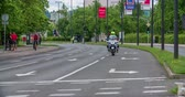 načasování : MARATON FRANJA 2016: A policeman on a motorcycle is dirivng through the streets and ahead of the cyclists that are competing in a race. Close-up shot. It is a nice summer day. Dostupné videozáznamy