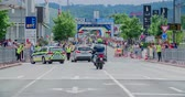 načasování : MARATON FRANJA 2016: Two police cars and a motorcyclist are driving on a road ahead of all the road bicycle contestants. Wide-angle shot. Dostupné videozáznamy