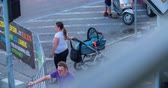 načasování : MARATON FRANJA 2016: A woman is waiting with a trolley and a baby inside by the side of the road. They are watching the cyclists. Wide-angle shot.
