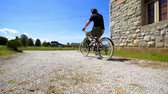 sacral : A young man is riding his bicycle away from the church to the main street. It is a nice summer day for cycling. Stock Footage