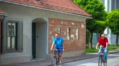 local de nascimento : Two people on bicycles are passing by Plecnik House. It is a very nice summer day. Close-up shot.