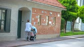 local de nascimento : Two women are passing by Plecnik House. They are going to opposite directions. It is summer time. Wide-angle shot. Stock Footage