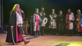 cavaleiro : A king is talking on stage and he is holding a microphone. The knights are standing on the side.