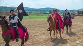 cavaleiro : Three noblemen on horses are walking one after the other across the field and one of them is also carrying a flag in his hands. It is a warm summer day.